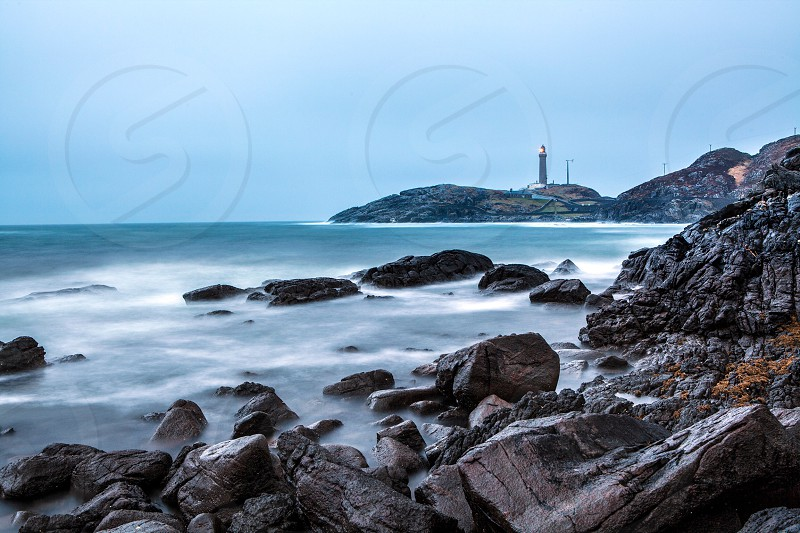 lighthouse on a hill across the rocky beach cove photo