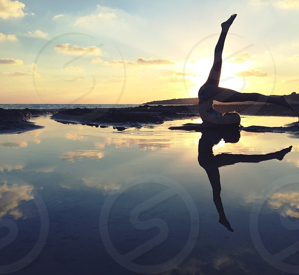 sunset behind woman doing yoga on water photo