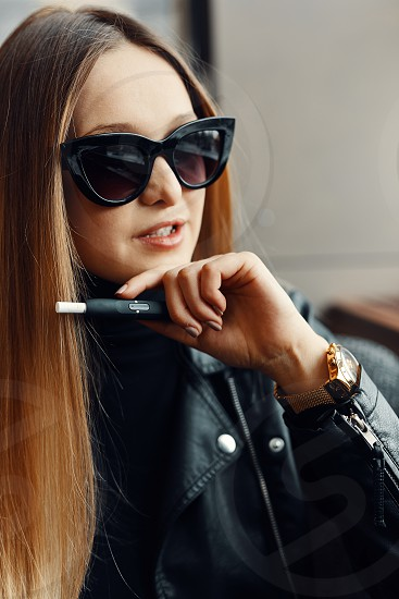 Girl sit in caffee place and smoke electronic cigarette wear glasses photo