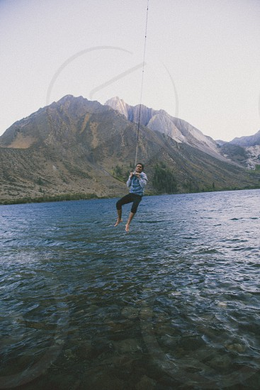 man in gray jacket black pants jumping into the water photo