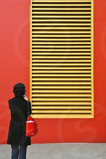 Back of woman in front of red wall with yellow vent.  photo