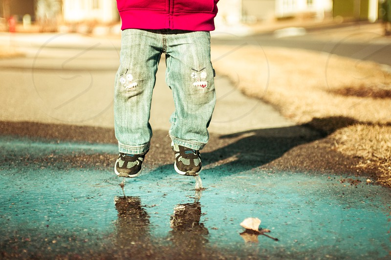 sensory boy youth child jump jumping play jeans shoes leaf puddle water hang time blue jeans fun patches knees sweatshirt red photo