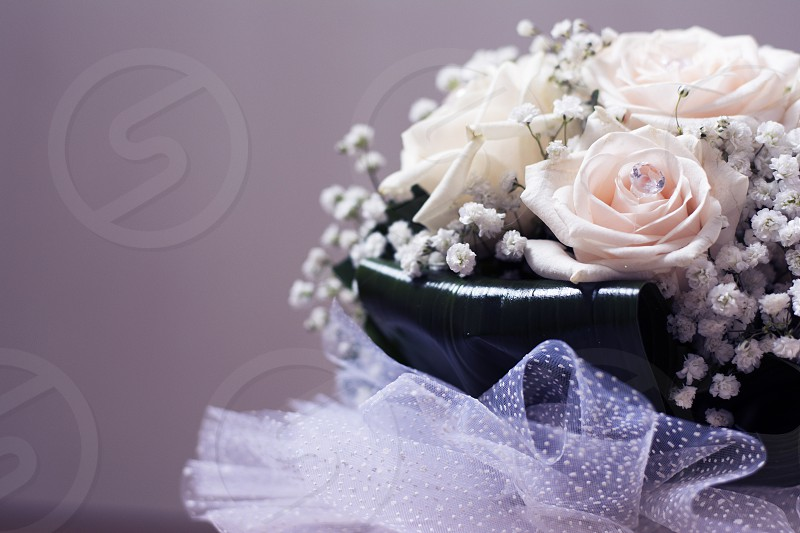 Wedding bouquet full of white roses with crystal on it closeup photo