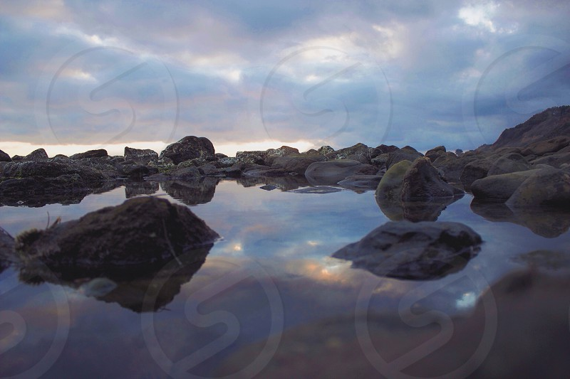 rocks in water under cloudy sky photo