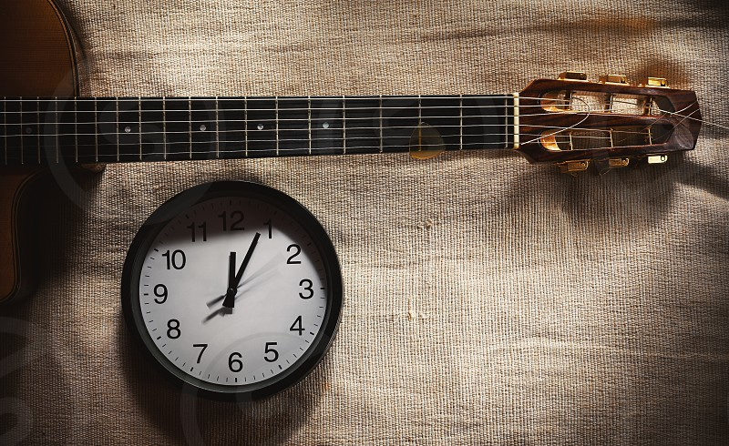 Simple composition black wall clock on bed blanket showing twelve o'clock and part of an old retro gypsy style acoustic guitar.   photo