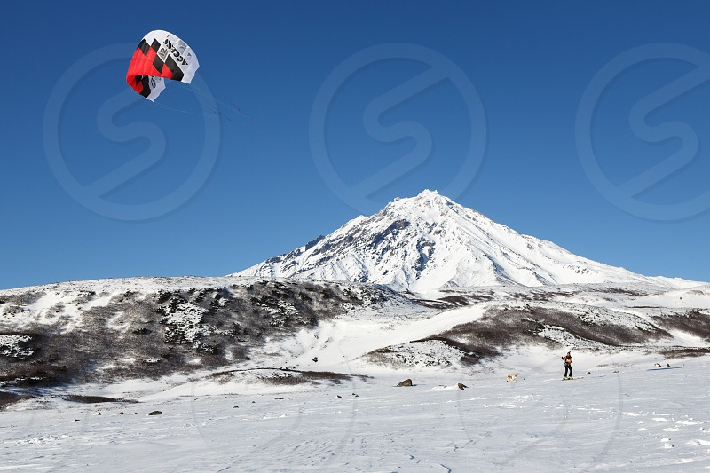 KAMCHATKA KORIAKSKY VOLCANO RUSSIA - NOVEMBER 22 2014: Snowkiting or kiteboarding - sportsman glides on skis on snow on a background of active Koriaksky Volcano (Koryaksky Volcano) on sunny day. photo