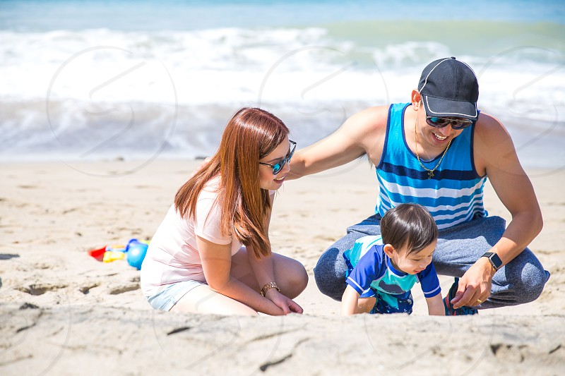 man in black white and blue tank top and blue denim pants near  boy in blue and teal crew neck shirt beside a woman in pink crew neck shirt watching the beach sand during daytime photo
