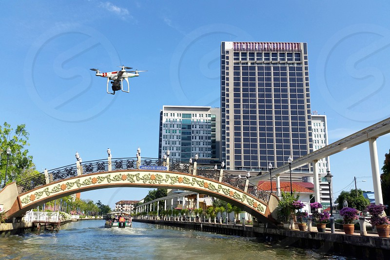 low view photo of a white drone quadcopter near bridge and a 3 high rise building during daytime photo