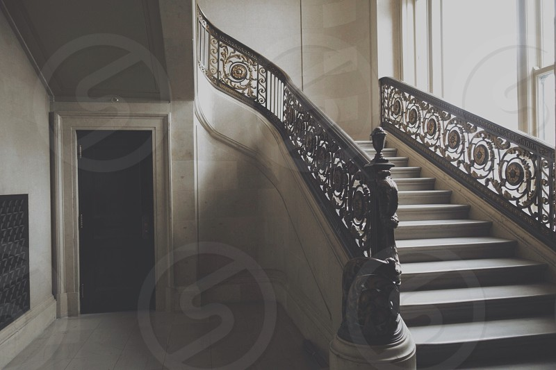 white stairs with black wooden floral railings photo