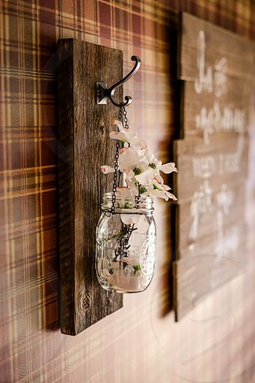 Glass canning jar used in rustic wall decor on plaid wall with rough barn board wood and white flowers photo