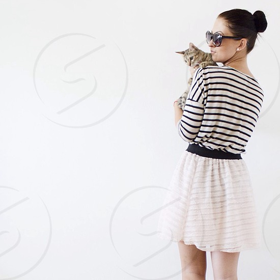 woman in white and black stripe 3/4 sleeved shirt and white skirt carrying brown tabby cat photo