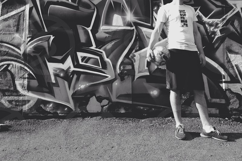 grayscale photo of man in t-shirt and shorts holding soccer ball standing in front of graffiti wall photo