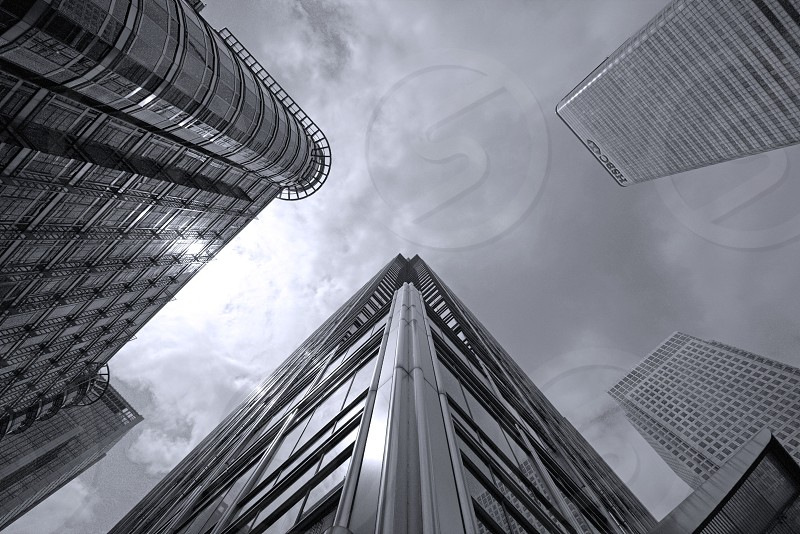 Giants in Canada Square. London Canary Wharf architecture buildings black and white from below metal and glass wide angle natural light photo