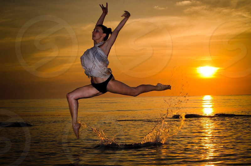 woman dancing ballet on blue body of water during orange sunset photo