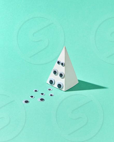 Geometric gupsum pyramid with eye pupils on a brink and on a light turquoise background with hard shadows and place for text. Halloween simbol of holiday party. photo