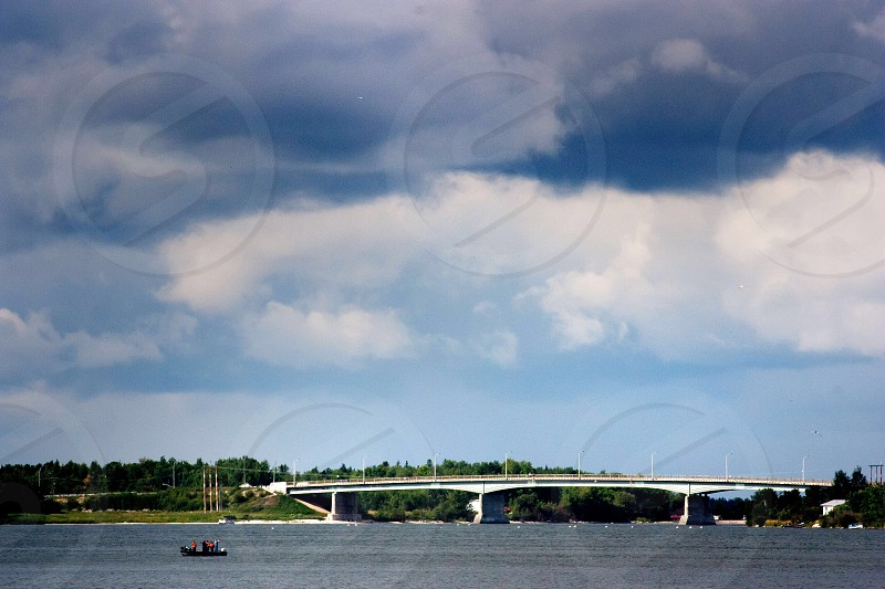 sail boat rowing towards white bridge under gray clouds photo