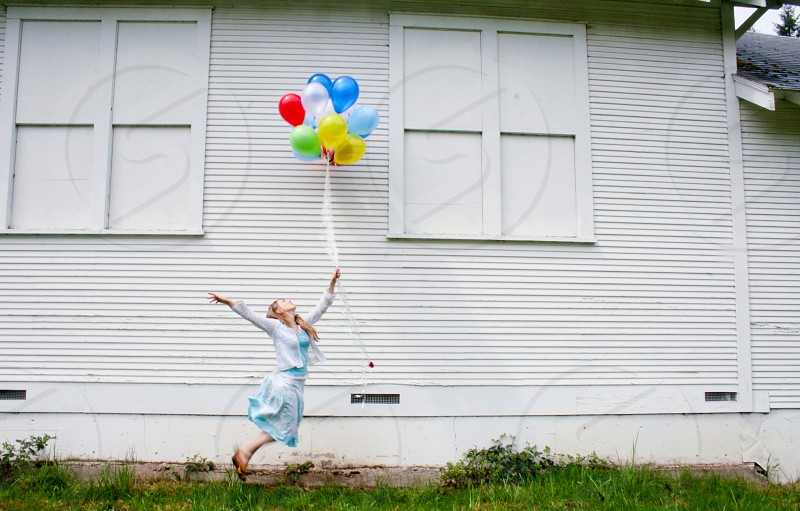 girl in grey and teal long sleeve dress jumped and holding a bundle of balloons near white wall photo