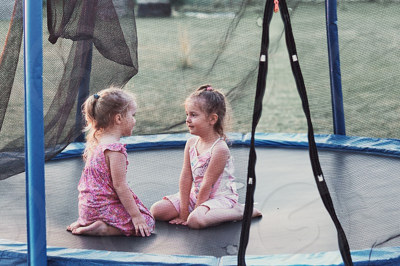 Two little cute girl talking sitting and playing on trampoline in backyard on summer day photo