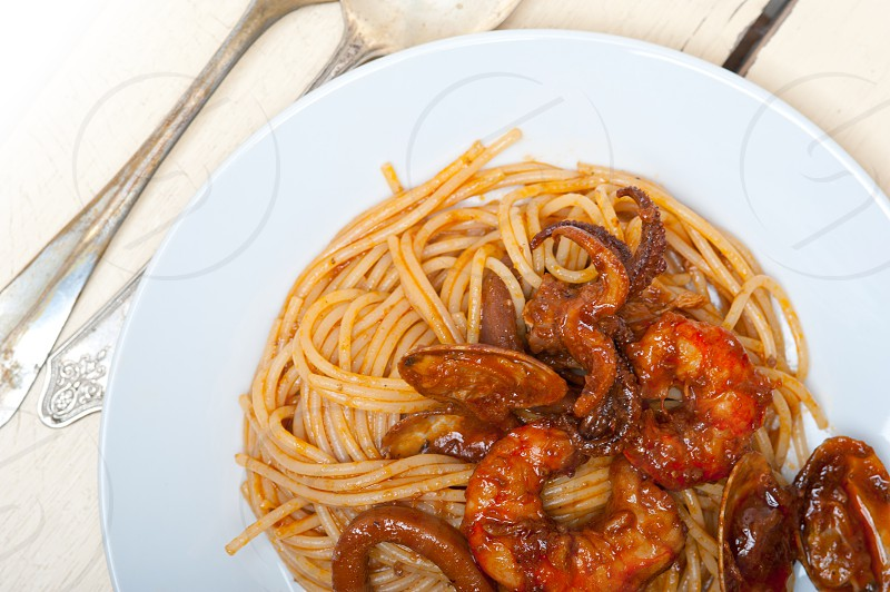 Italian seafood spaghetti pasta on red tomato sauce photo