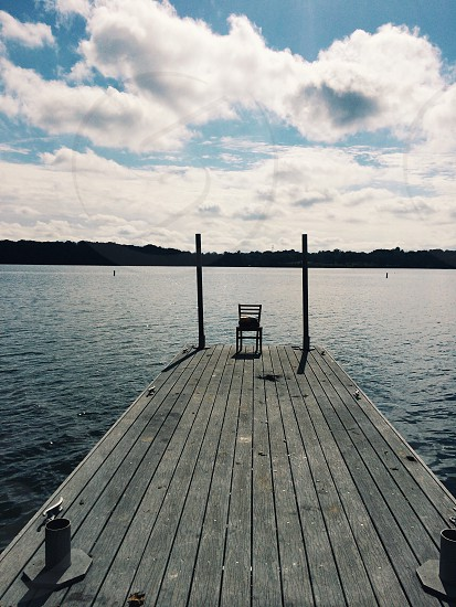 black chair at the edge of brown wooden dock photo