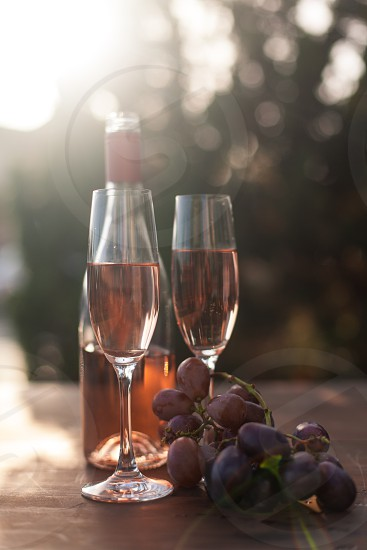 two champagne flutes filled with rose wine next to the bottle and purple tables grapes surrounded by trees under the sun photo