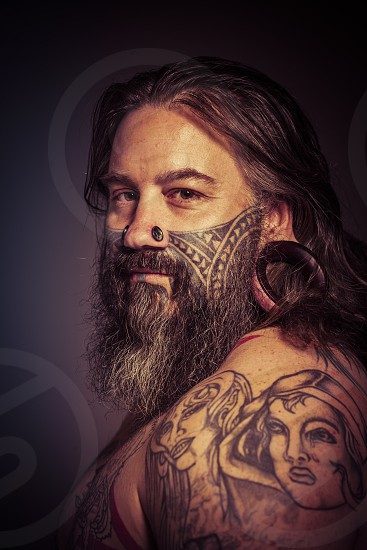 Tattooed man with stretched earlobes  photo