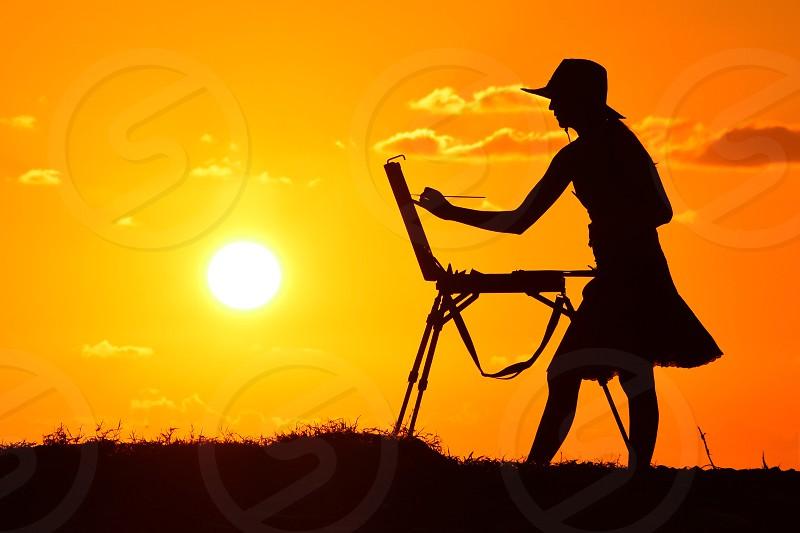 silhouette of woman painting under orange sunset photo
