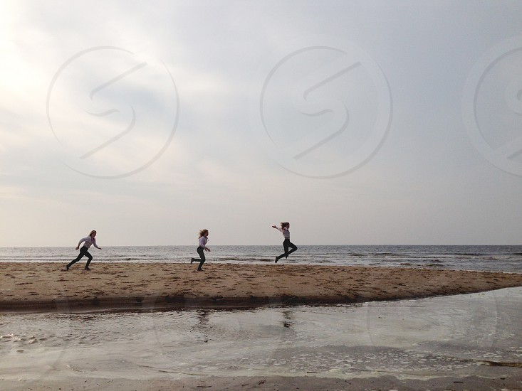three women running towards the ocean photo