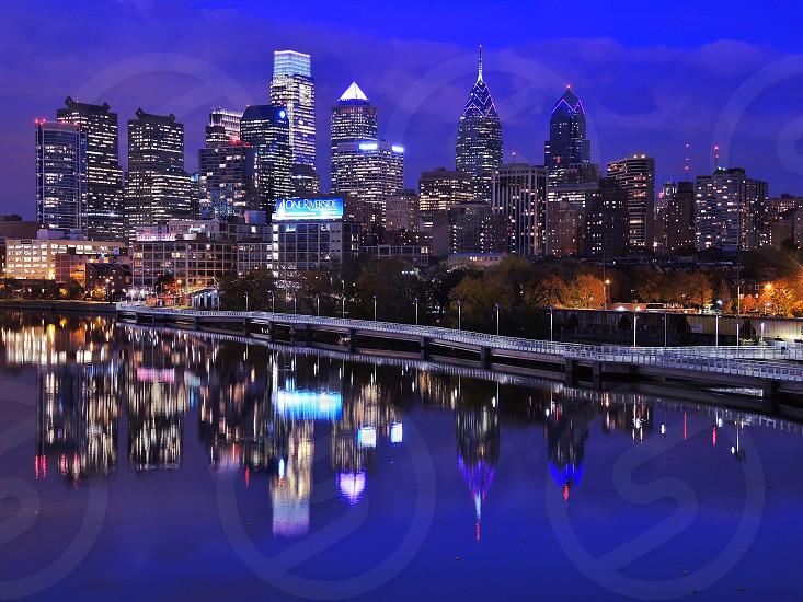city skyline at night near river photo