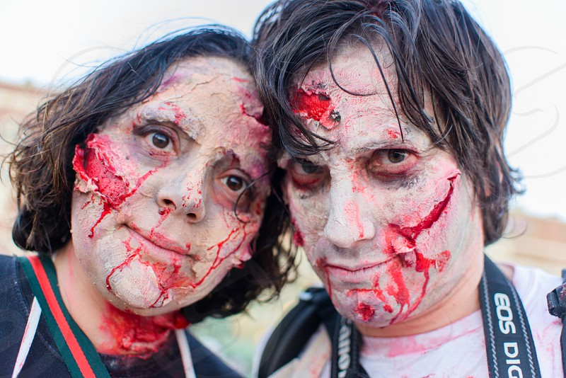 man and woman with zombie makeup smiling photo