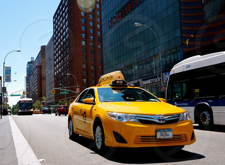 yellow taxi cab on vehicular road photo