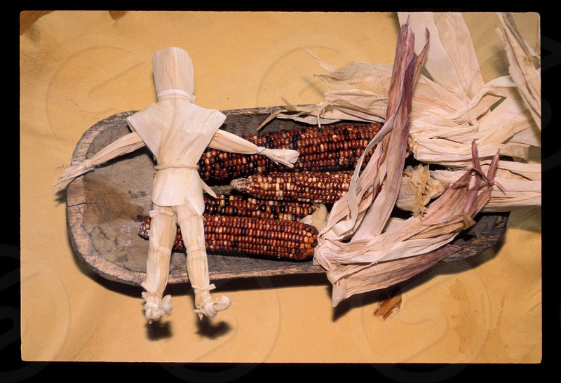 Colorful speckled Indian corn in a Navajo wooden bowl traditionally was a staple food among various tribes. The husks were used to make various objects such as this corn husk doll photo