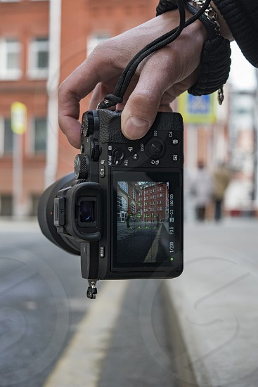 A close up view of a male hand holding a digital camera vertically taking picture of street and buildings photo