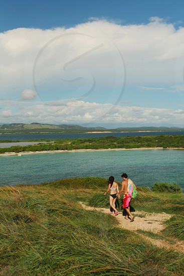 A young couple follow a trail to the beach together on a sunny day. photo
