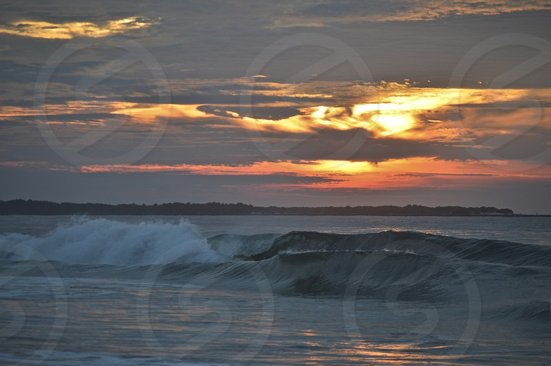 Fiery sunrise over rolling waves Cape May NJ photo