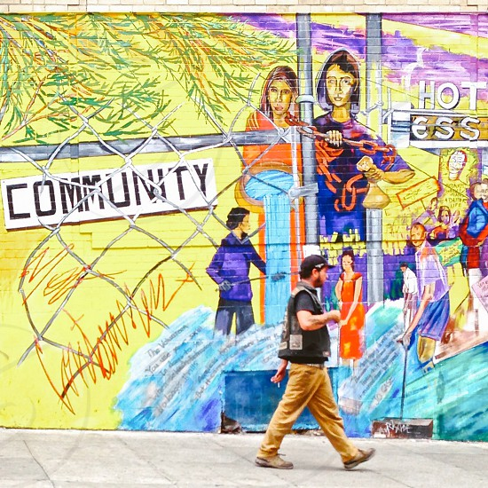 large mural of community and man walking by photo
