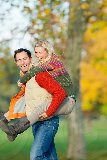 Couple enjoying piggyback ride in autumn park photo
