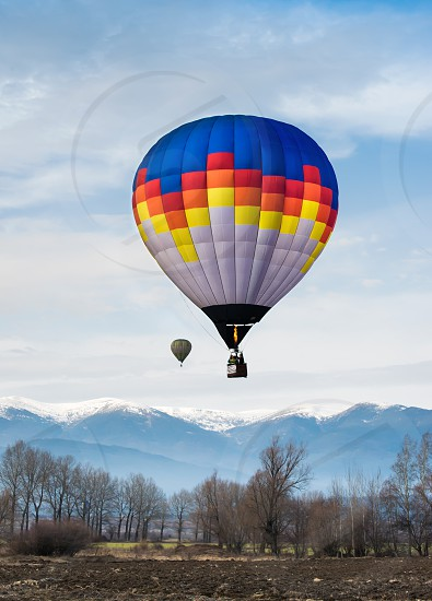 Multicolored Balloon in the blue cloudy sky. Mountain background photo