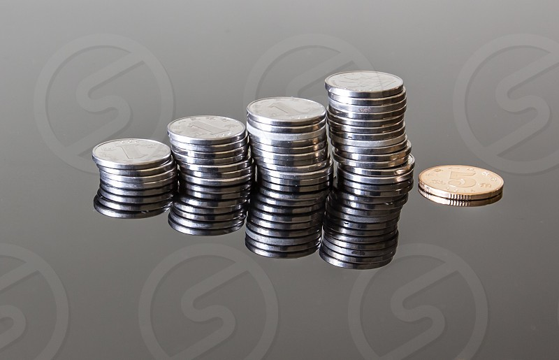 reflective photography of pile of silver round coins on top of table photo