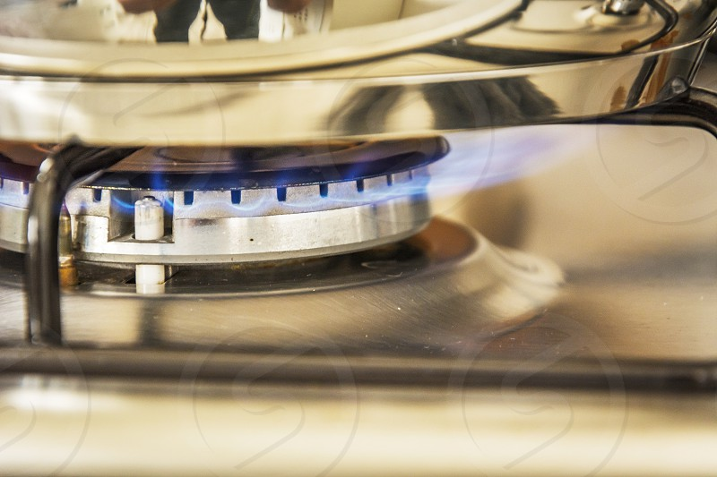 Focus of blue flame gas on a cooker boiling pot in kitchen gas stove. Cooking Food. photo