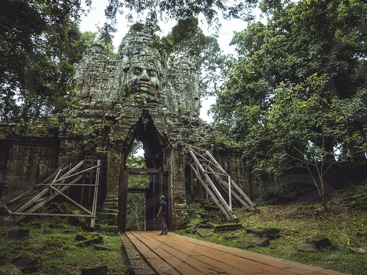Dwarfed by the mighty gate at Angkor Wat temple complex. photo
