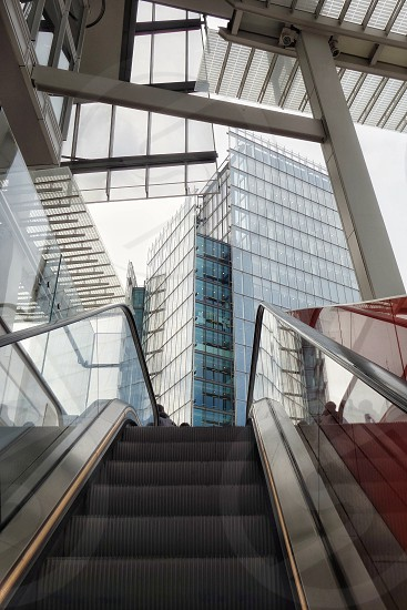 A view upwards from an escalator towards office tall building... photo