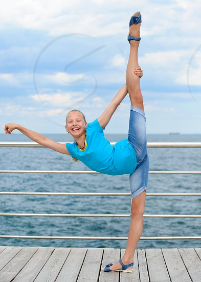 Happy girl stretching out making vertical split. Cloudy sky and sea in background photo