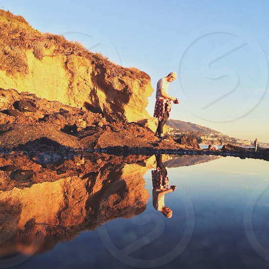 man photographing water pool at golden hour  photo