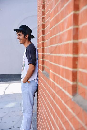 Man brick wall hat photo