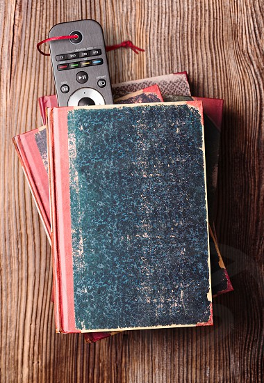 Stack a few books on wooden table with bookmark in shape of tv remote inserted in one book photo