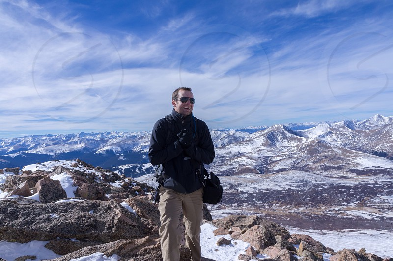 man in khakis and black coat on top of snowy mountain photo