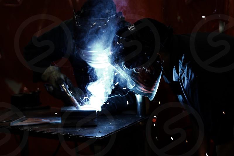 2 man with welding helmet photo