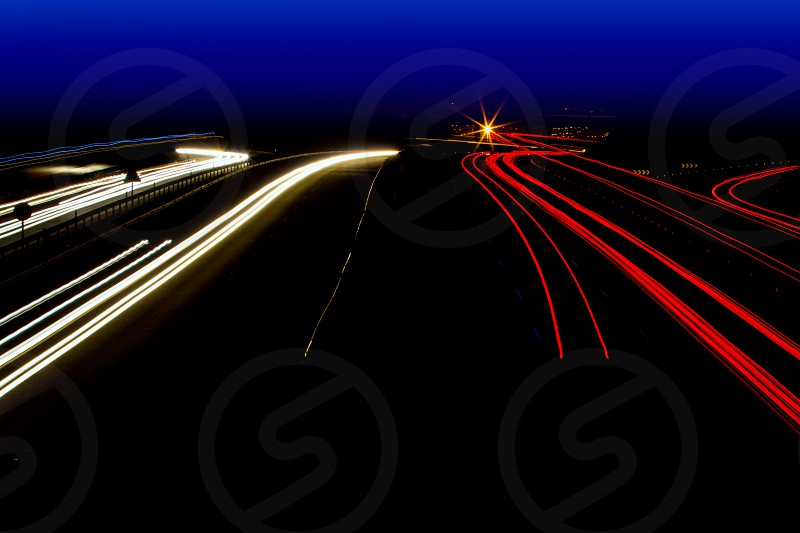 car light trails in red and white on night road curve photo