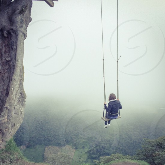 woman in black on a swing in a gorge photo